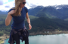 Blond woman standing on a mountain wearing The Greenest Tee on the Planet by Kusaga Athletic
