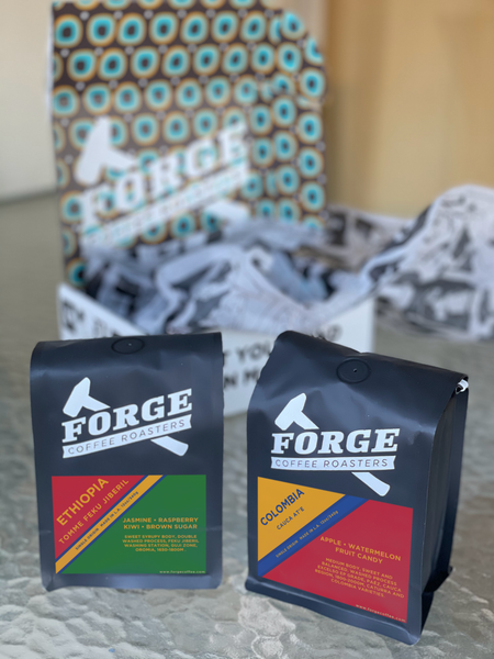 two bags of coffee in front of special holiday packaging