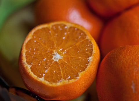 close up photo of beautiful orange fruit sliced in half, revealing starred segments inside