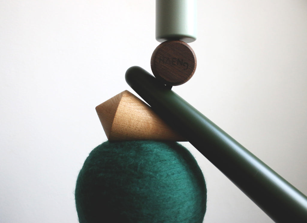 A close-up photo of the green merino wool, tornado oak, green stick, wenge logo and a green mint cylinder