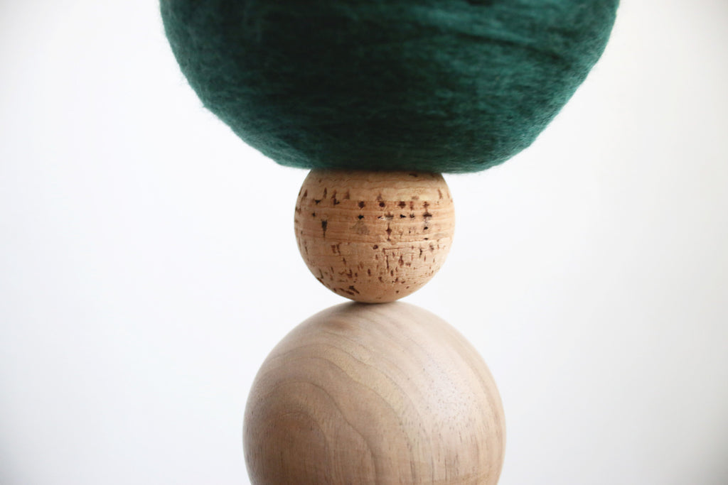 A close-up photo of the walnut socket, kork element and green merino wool sphere