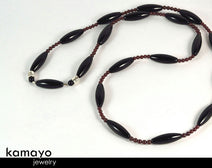 "CAPRICORN LARIAT NECKLACE <span class=""subtitle"">- Large Rice Black Onyx Beads and Red Garnet </span><span class=""findings"">- Stainless Steel Findings </span><span class=""length"">- 36 Inches </span>"