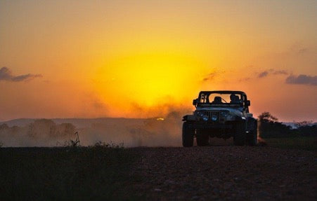 An off-road vehicle on a dusty track at sunset