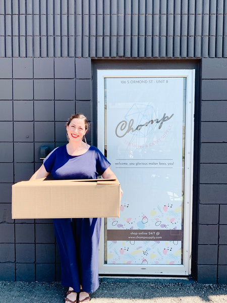 A woman holding a moving box in front of the new HQ for Chomp Supply Inc.