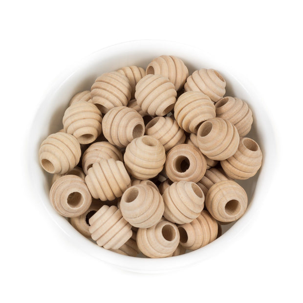 A bowl of natural maple wood teething beads that have a beehive like texture to them