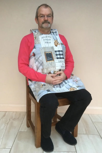 Dining drApron® to protect clothing whilst eating. Much more dignified and attractive than adult bib. Fabulous and engaging design with baking utensils in smart neutral beiges and greys with a flash of red. Looks equally good on men or women.