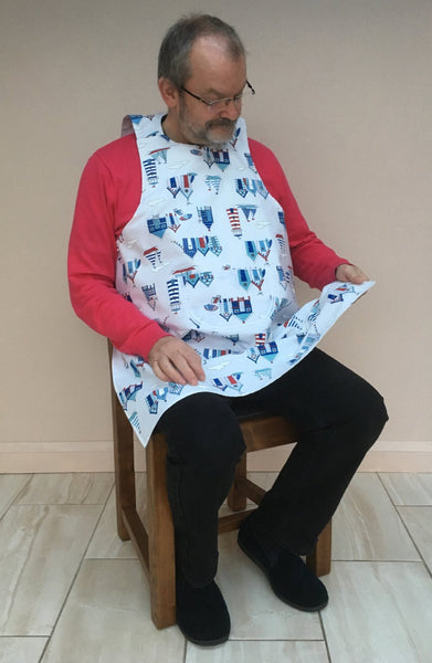 Beach Huts design Dining drApron® to protect clothing whilst eating. Much more dignified and attractive than adult bib. Fabulous and engaging design with beach huts and lighthouses in smart blues, navy and red. Looks equally good on men and women.
