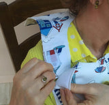 Showing hook and loop fastening on neck of dining drApron® to protect clothing whilst eating. Much more dignified and attractive than adult bib. Fabulous and engaging design with beach huts and lighthouses in smart blues, navy and red. Looks equally good on men and women.