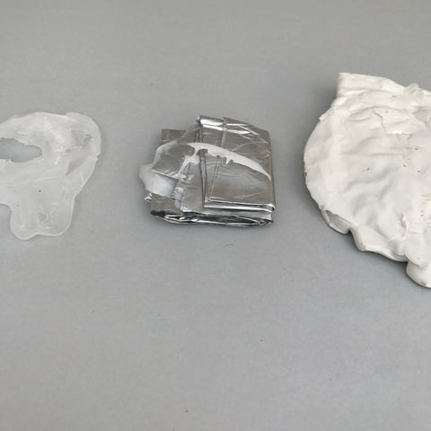 A picture of a melted Aluminium Refill pack (Dirt) sandwiched by a plastic scoop and melted bottle