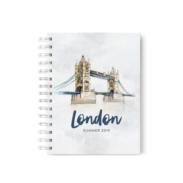 spiral-bound hardcover travel journal with watercolor illustrations of world landmarks