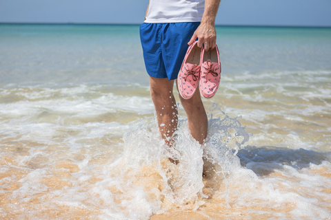 man in beach water holding a pair of pink boat shoes