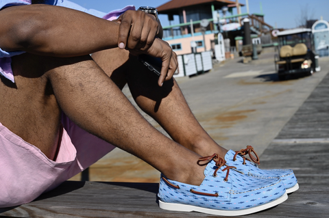 man sitting on a dock with blue boat shoes