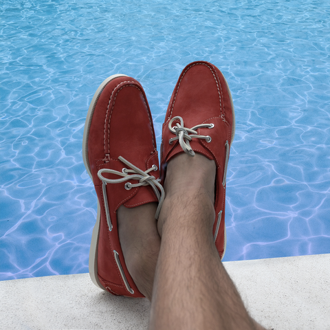 man sitting beside the pool wearing froats red boat shoes
