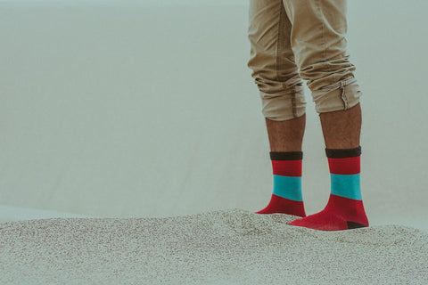 Man wearing red and green socks in the sand