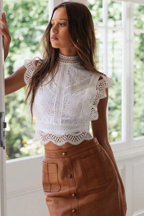 Girl looking out on the window wearing the Aylana Lace Crochet Top and camel colored mini skirt.