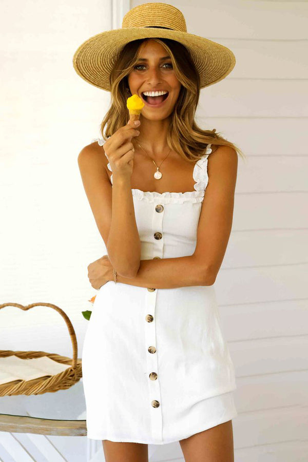 Girl eating ice cream on a cone wearing the white Arlo Ruffles Strap Mini Dress, straw hat and coin necklace.
