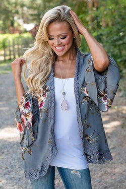 Girl wearing the gray Darcee Floral Fluted Cardigan, white top, ripped denim jeans and boho necklace.