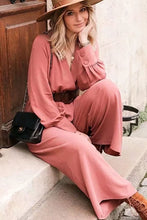 Load image into Gallery viewer, Girl sitting on stairs wearing her Dayna Belted Jumpsuit, bohemian brown hat, black shoulder bag and brown suede lace up boots.