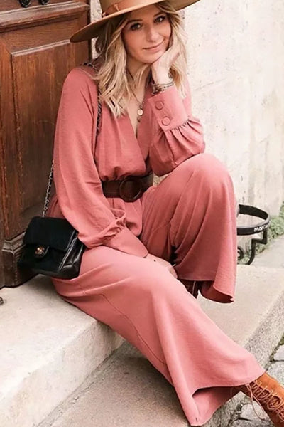 Girl sitting on stairs wearing her Dayna Belted Jumpsuit, bohemian brown hat, black shoulder bag and brown suede lace up boots.