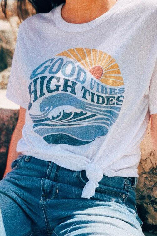 Model wearing white Good Vibes High Tides T-Shirt and blue denims.