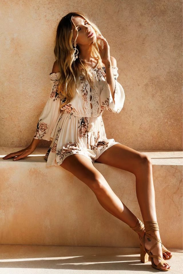 Girl stiing on a ledge wearing the Adelle Soft Peach Romper, brown sandals and boho statement earrings.
