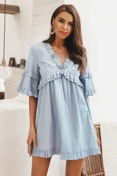 Girl wearing the Linda Ruffled Babydoll Dress paired with boho earrings and gold necklace.