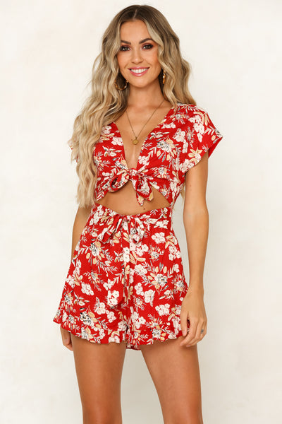 Girl wearing the Chasing Florals Red Playsuit paired with gold jewelries.