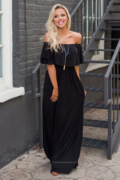Girl standing near a staircase wearing the black Olivia Flounce Maxi Dress and boho necklace.