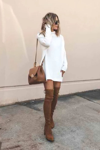 Standing girl wearing white Reily Knitted Sweater Dress, brown over the knee boots, brown shoulder bag and black sunglasses.