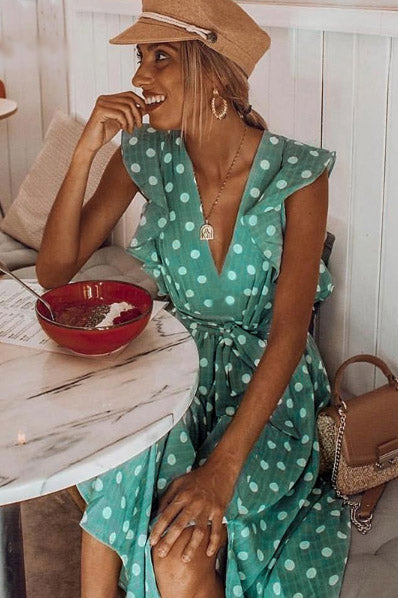 Girl sitting on a dining area wearing the Sabella Dotted Midi Dress, brown baker boy hat, brown shoulder bag and gold jewelries.