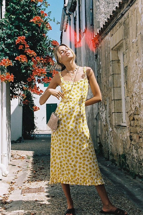 Girl wearing the Solest Floral Midi Dress, small crossbody bag and layered gold and choker shell necklaces.
