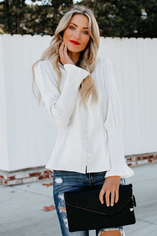 Girl wearing the Adelfa Shirred White Shirt, black clutch and ripped jeans.