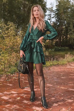 Load image into Gallery viewer, Girl looking festive wearing her Wynona Ruffled Green Dress, black tights, black boots and black hand bag