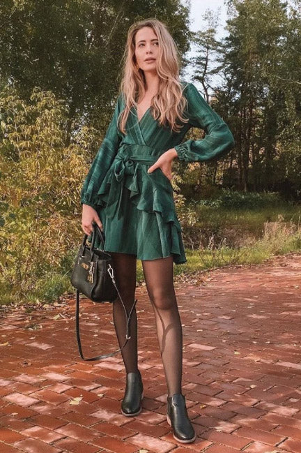 Girl looking festive wearing her Wynona Ruffled Green Dress, black tights, black boots and black hand bag