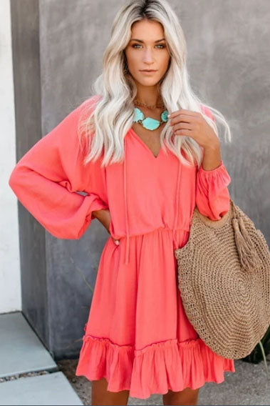 Girl wearing the coral Ylac Ruffled Hem Mini Dress, boho turquoise earrings and rafia bag.
