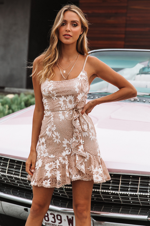 Girl standing in front of a car wearing the Arci Lace Mini Dress and layered gold necklaces.