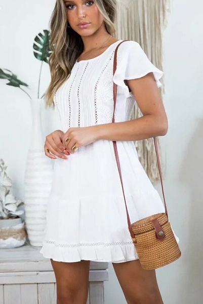 Girl wearing the Arya Mini Dress paired with boho straw bag.
