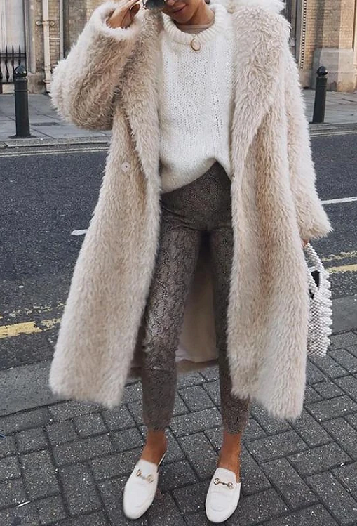 Girl standing on a side walk wearing her Carlien Faux Fur Coat, white sweater, snake print leggings and white mules