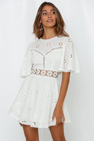Girl wearing the Cleo White Eyelet Dress paired with boho drop earrings.