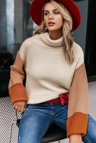 Girl sitting wearing Dierdre Colorblock Turtleneck Sweater, red hat, red belt bag  and jeans.