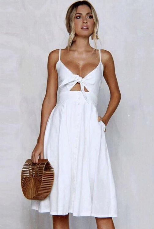Girl wearing the white Emery Tie Front Midi Dress paired with wooden hand bag.