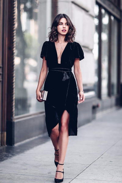 Girl wearing the Maribelle Black Velvet Dress, black shoes, dainty horn necklace and clutch.