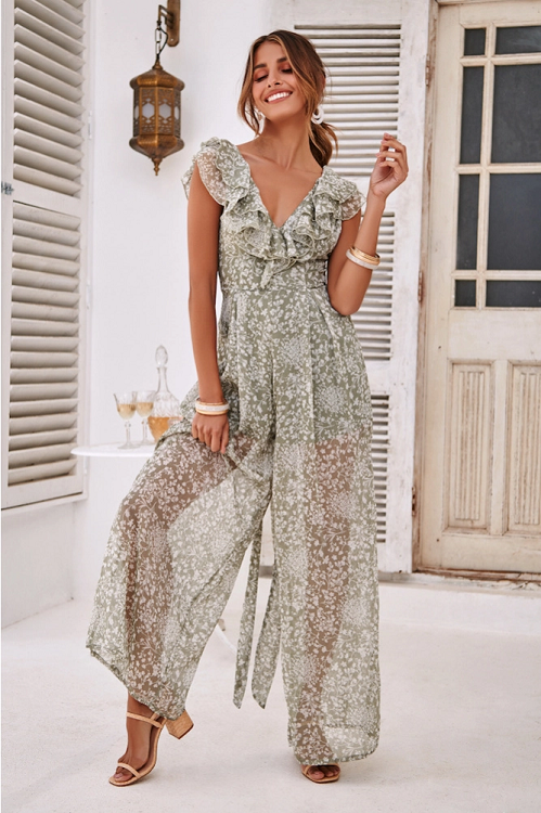 Girl wearing the sage colored Eyva Ruffled Chiffon Jumpsuit, nude block heel sandals and boho jewelries.