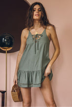 Load image into Gallery viewer, Girl wearing the army green Melati Lace-Up Mini Dress, gold jewelries and wooden hand bag.