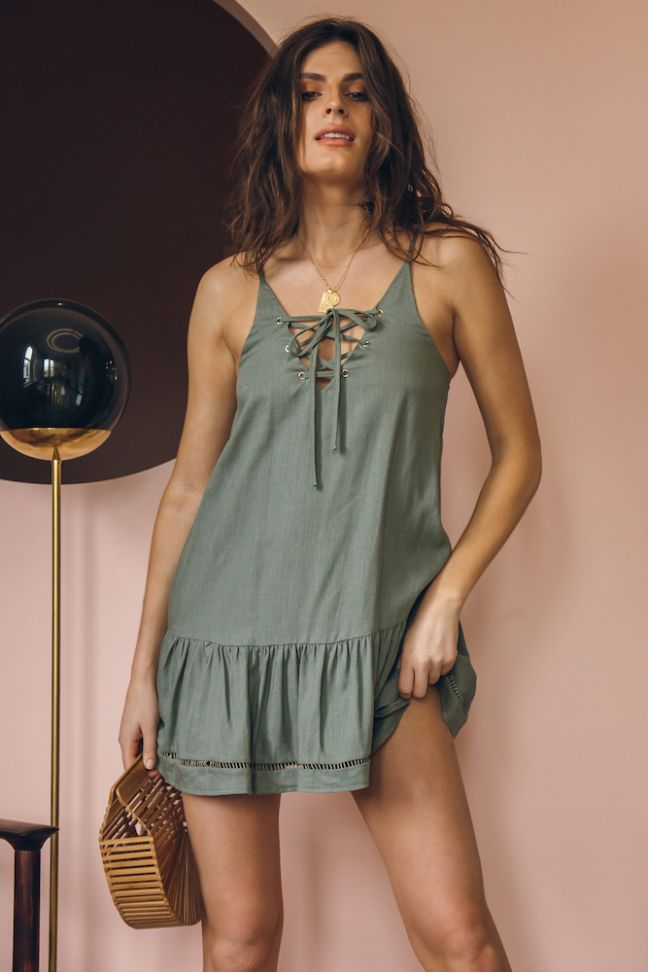 Girl wearing the army green Melati Lace-Up Mini Dress, gold jewelries and wooden hand bag.