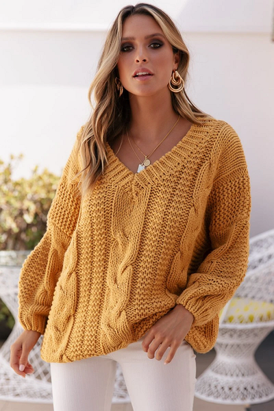 Girl wearing mustard Jaana V-Neck Cable Knit Sweater, white jeans and layered necklaces.