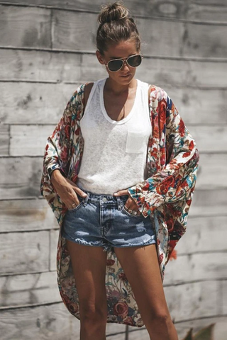 Girl wearing the Lisa Floral Cardigan, white top, denim shorts and black sunglasses.