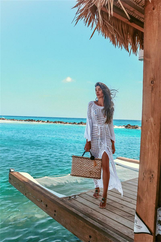 Girl wearing the Margot Crochet Beach Dress, boho sandals and woven bag.
