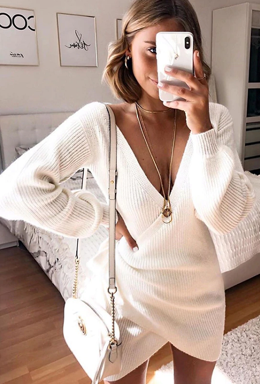 Girl taking self photo wearing her white Marva Wrap Sweater Dress, white shoulder bag and boho jewelries.