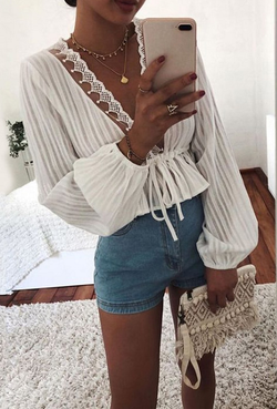 Girl holding a mobile phone wearing the Nadya Striped Peplum Top, blue denim shorts, boho jewe;ries and boho wrist bag.